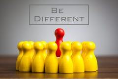 Soyez concept différent avec des figurines de gage sur la table images stock