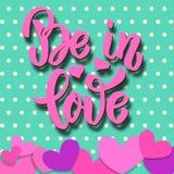 Soyez dans l'amour Expression de lettrage sur le fond coloré avec les coeurs de papier Thème de jour de valentines Concevez l'élé Photographie stock