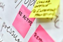 Soyez en activité écrit sur les autocollants de papier roses et jaunes attachés à un tableau de conférence photo libre de droits