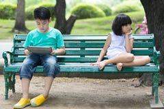Soyez en conflit entre le frère et la soeur asiatiques s'asseyant sur un woode Photo stock