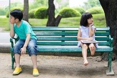 Soyez en conflit entre le frère et la soeur asiatiques s'asseyant sur un woode Image libre de droits