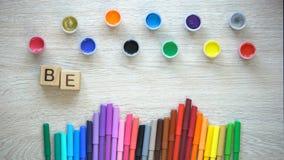 Soyez expression créative faite de cubes, stylos feutres colorés et table menteuse de peintures banque de vidéos