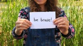 Soyez fille courageuse et belle montrant des mots banque de vidéos