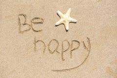 Soyez heureux écrit sur le sable blanc, fond de plage images libres de droits
