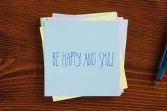Soyez heureux et sourire manuscrit sur la note Photographie stock