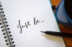 SOYEZ JUSTE main-en lettres dans le carnet photo stock