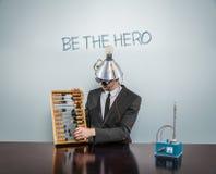 Soyez le texte de héros sur le tableau noir avec l'homme d'affaires Image stock