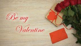 Soyez mon expression de valentines sur le fond avec le cadeau et les roses, main mettant l'enveloppe banque de vidéos
