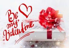 Soyez mon lettrage des textes de Valentine avec le boîte-cadeau blanc, arc rouge sur la neige avec le bokeh et chutes de neige Jo image libre de droits