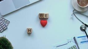 Soyez sain sur les cubes en bois arrêter le mouvement près du coeur de jouet sur la table, médecine clips vidéos