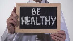 Soyez texte sain sur le tableau noir dans des mains de docteur, système immunitaire, mode de vie actif clips vidéos