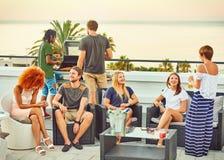 Sozialinteraktion unter einer attraktiven Gruppe frineds während des Grills lizenzfreies stockfoto