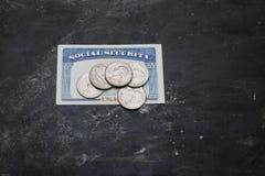 Sozialversicherungskarte mit Münzen auf ihr Lizenzfreie Stockfotografie