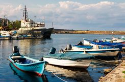 Fishing boats in port of Sozopol at sunset. SOZOPOL - AUGUST 19: fishing boats at sunset on August 19, 2015 in Sozopol, Bulgaria. small fishing boats and few big royalty free stock photography