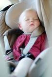 Spädbarn behandla som ett barn att sova i ett bilsäte Arkivfoto