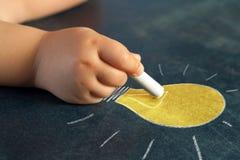 Spädbarn räcker att dra en ljus kula. Fotografering för Bildbyråer