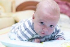 Spädbarn som ligger och ser Royaltyfri Fotografi
