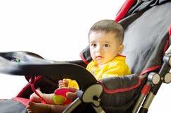 Spädbarn som spelar på den svarta & röda sittvagnen Royaltyfri Foto