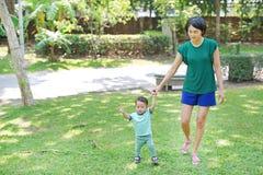 Spädbarnet behandla som ett barn att lära att gå med hans moder på det gröna gräset f?rsta steg fotografering för bildbyråer