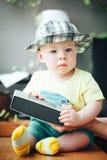 Spädbarnet behandla som ett barn barnpojkehalvåret som är gammalt med den solida högtalaren Arkivfoton