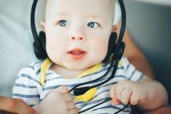 Spädbarnet behandla som ett barn barnpojkehalvåret som är gammalt med hörlurar Royaltyfria Foton