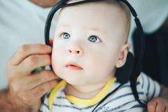 Spädbarnet behandla som ett barn barnpojkehalvåret som är gammalt med hörlurar Arkivfoto