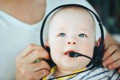 Spädbarnet behandla som ett barn barnpojkehalvåret som är gammalt med hörlurar Arkivbilder