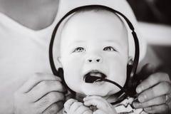 Spädbarnet behandla som ett barn barnpojkehalvåret som är gammalt med hörlurar Royaltyfri Fotografi
