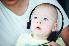 Spädbarnet behandla som ett barn barnpojkehalvåret som är gammalt med hörlurar Royaltyfri Bild