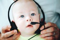 Spädbarnet behandla som ett barn barnpojkehalvåret som är gammalt med hörlurar Fotografering för Bildbyråer