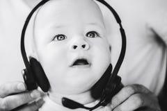 Spädbarnet behandla som ett barn barnpojkehalvåret som är gammalt med hörlurar Royaltyfri Foto