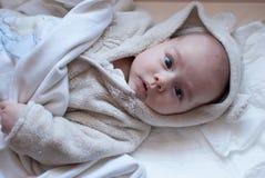 Spädbarnet behandla som ett barn flickan i badrock Arkivbild
