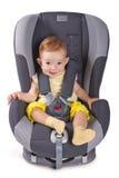 Spädbarnet behandla som ett barn flickasammanträde i ett bilsäte Royaltyfri Fotografi