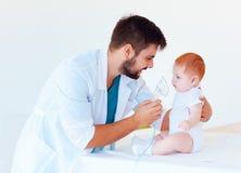 Spädbarnet behandla som ett barn mottar en nebulizerbehandling till och med den ansikts- maskeringen Arkivfoto