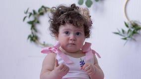 Spädbarnet på fotoperiod i rosa färgklänning poserar med en blomma i händer in i studionärbild lager videofilmer