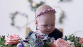 Spädbarnsålder barnflicka sitter i blommor på fotofors i studio med garnering stock video