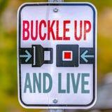 Spänna fast upp och bo vägmärket för säker körning arkivbild