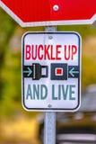 Spänna fast upp och bo vägmärket på en solig gata arkivbild