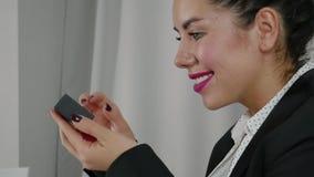 Spännande öppnar en ung kvinna i en affärsdräkt en gåva stock video
