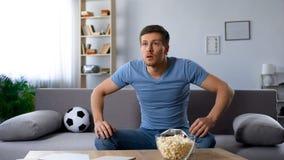 Spännande fotbollsfan som håller ögonen på uppmärksamt spelare på fält på tv, halv-final arkivfoto