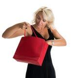 Spännande kvinna som ser den inre shoppingpåsen Arkivbild