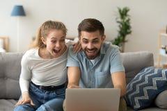 Spännande par som chockas av oväntad online-seger royaltyfri fotografi