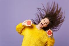 Spännande ung kvinna med flödande hår som håller öppna rymmande halfs för mun av den nya mogna grapefrukten som isoleras på viole royaltyfri foto