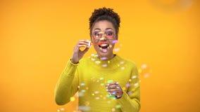 Spännande ung kvinna som blåser såpbubblor, barnsligt lynne, bekymmerslös lycka royaltyfri bild