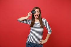 Spännande ung kvinna som vitt håller munnen öppen och att se förvånat och att täcka ögat med kreditkorten som isoleras på ljust r fotografering för bildbyråer