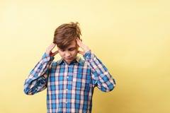 Spänning huvudvärk, meningsöverbelastningspojke som griper huvudet royaltyfria foton