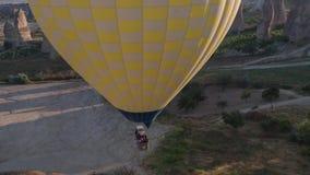 Spännvidden av en stor gul ballong, i en korg av folk, närbild Flyg över bergen - panorama av Cappadocia stock video