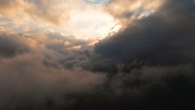 Spännviddkamera till och med aftonregnmolnen på solnedgången ovanför molnnivåer Sagolikt flyg i molnen flyg- sikt arkivfilmer