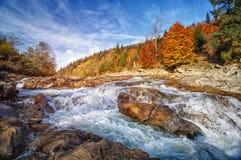 Späte Herbst-Landschaft Ein stürmischer Gebirgsfluss mit Steinen in den Bergen Stockfoto