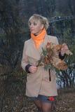 Spätherbst im Wald, Waldsee, blondes Mantelmädchen durch den See Stockbilder